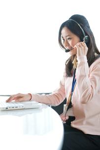 インカムで話をしながらPCを使う女性オペレーターの写真素材 [FYI02069099]