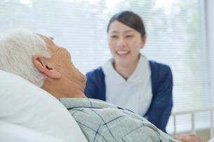 ベッドで横になるシニア男性と笑顔で話す看護師の写真素材 [FYI02069102]