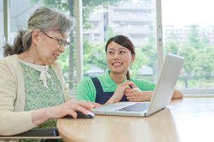 介護施設でノートパソコンを使うシニア女性と女性介護士の写真素材 [FYI02069108]