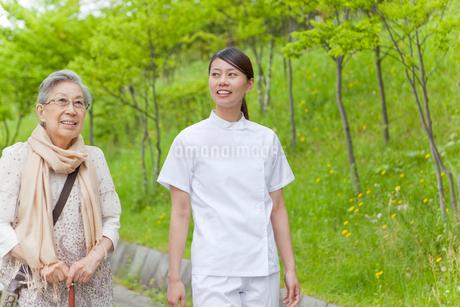 公園を散歩するシニア女性と女性介護士の写真素材 [FYI02069109]