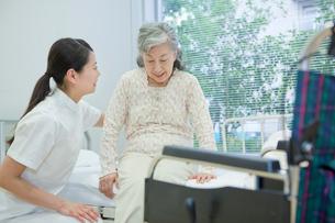 ベッドで横になるシニア女性を介助する女性介護士の写真素材 [FYI02069114]