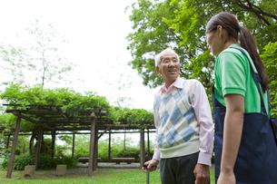 シニア男性と公園を散歩する女性介護士の写真素材 [FYI02069117]