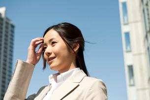 オフィス街で髪の毛をかきあげるスーツ姿の女性の写真素材 [FYI02069118]