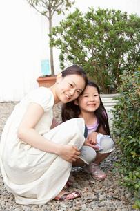 庭で寄り添ってしゃがんでいる母親と娘の写真素材 [FYI02069122]