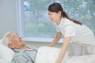 ベッドで横になるシニア男性を介助する女性介護士の写真素材 [FYI02069138]