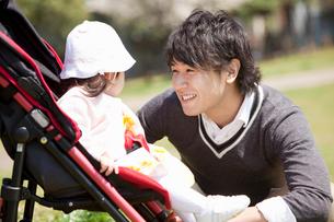ベビーカーに乗った赤ちゃんに話しかける若い父親の写真素材 [FYI02069149]