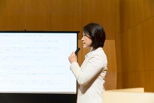 スクリーンの前でマイクを持って話すスーツ姿のミドル女性の写真素材 [FYI02069151]