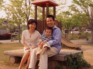 公園のベンチに座る家族3人の写真素材 [FYI02069158]