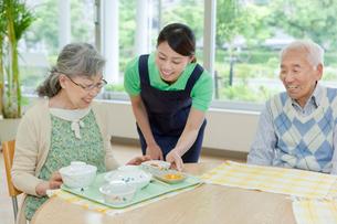 介護施設でシニア女性に食事を配膳する女性介護士の写真素材 [FYI02069168]