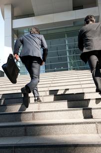 ビルの階段を駆け上がる2人のビジネスマン達の写真素材 [FYI02069169]