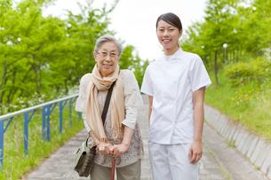 笑顔でこちらを見る女性介護士とシニア女性の写真素材 [FYI02069170]