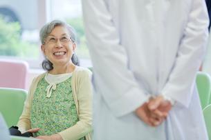 病院のロビーで笑顔で医師と会話するシニア女性の写真素材 [FYI02069173]