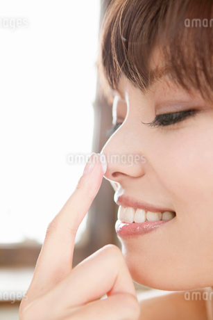 鼻にスキンクリームを塗る若い女性の横顔の写真素材 [FYI02069178]