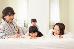 ベッドの上で仲良く寝転ぶパジャマ姿の4人家族の写真素材 [FYI02069184]