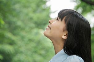 公園で空を見上げている若い女性の横顔の写真素材 [FYI02069186]