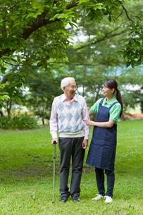 シニア男性と公園を散歩する女性介護士の写真素材 [FYI02069188]