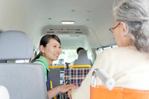 介護車両に乗る車いすのシニア女性と介護士の写真素材 [FYI02069189]
