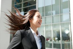 髪の毛をなびかせてオフィス街を走るスーツ姿の女性の写真素材 [FYI02069193]