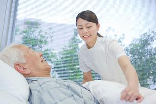 ベッドで横になるシニア男性を介助する女性介護士の写真素材 [FYI02069195]
