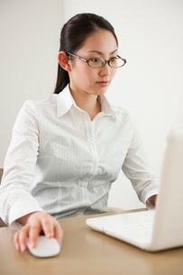 ノートPCを使い仕事をしている眼鏡の女性の写真素材 [FYI02069199]
