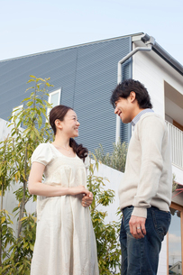 家の前で笑顔で向かい合う若い夫婦の写真素材 [FYI02069203]