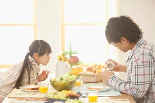 朝食の食卓につく娘と若い父親の写真素材 [FYI02069215]