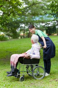 シニア男性の乗った車いすを押す女性介護士の写真素材 [FYI02069217]