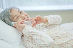 ベッドで横になり携帯電話で話しをするシニア女性の写真素材 [FYI02069223]