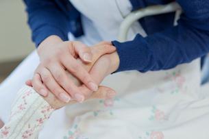 ベッドで横になるシニア女性の手を握る看護師の写真素材 [FYI02069229]