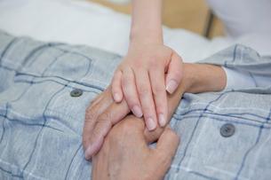 ベッドで横になるシニア男性の手に手を添える女性介護士の写真素材 [FYI02069236]