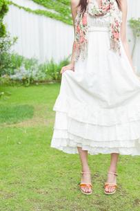 スカートをたくし上げる若い女性の足元の写真素材 [FYI02069241]