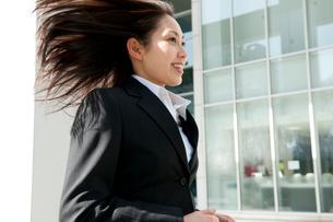 髪の毛をなびかせてオフィス街を走るスーツ姿の女性の写真素材 [FYI02069243]