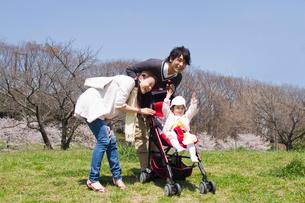 乳母車の赤ちゃんと公園を散歩する3人家族の写真素材 [FYI02069247]