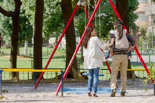 子供を背負って公園を散歩する3人家族の写真素材 [FYI02069268]