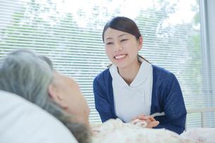 ベッドで横になるシニア女性の手を握る看護師の写真素材 [FYI02069273]