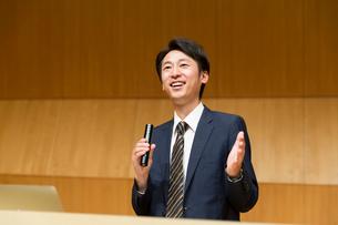 演台でマイクを持って話すスーツ姿の男性の写真素材 [FYI02069286]