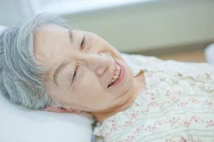ベッドで横になるシニア女性の写真素材 [FYI02069299]