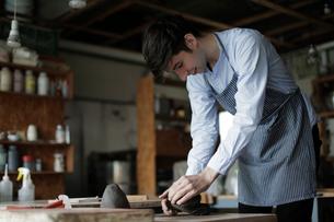 陶芸の粘土を練る外国人男性の写真素材 [FYI02069306]