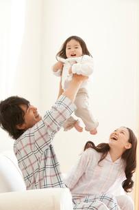 ソファで赤ちゃんを抱き上げる父親と笑顔で見守る母親の写真素材 [FYI02069313]