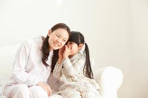 母親に内緒話をする娘の写真素材 [FYI02069317]