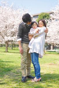 公園で赤ちゃんを抱く母親と寄り添う父親の写真素材 [FYI02069318]