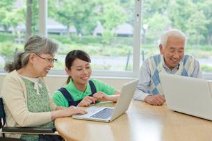介護施設でノートパソコンを使うシニアグループと女性介護士の写真素材 [FYI02069325]
