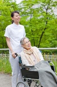 公園を散歩する車いすに乗ったシニア女性と女性介護士の写真素材 [FYI02069327]