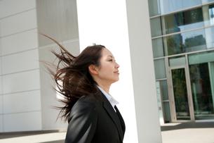 髪の毛をなびかせてオフィス街を走るスーツ姿の女性の写真素材 [FYI02069328]