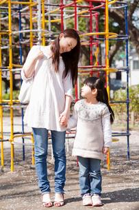ジャングルジムの前で手をつなぐ母親と子供の写真素材 [FYI02069334]