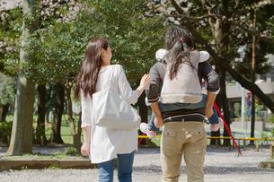 子供を背負って公園を散歩する3人家族の写真素材 [FYI02069335]