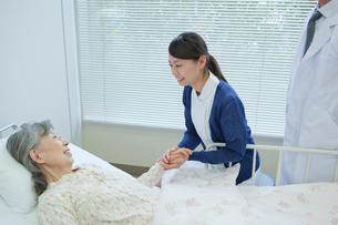 ベッドで看護師と笑顔で会話するシニア女性の写真素材 [FYI02069336]