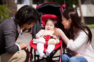 ベビーカーに乗った赤ちゃんと若い夫婦の写真素材 [FYI02069337]