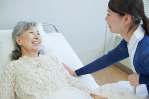ベッドで看護師と笑顔で会話するシニア女性の写真素材 [FYI02069341]