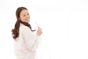パジャマ姿で振り返る女性の写真素材 [FYI02069342]